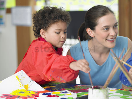 School : Art teacher squatting next to boy painting in art class