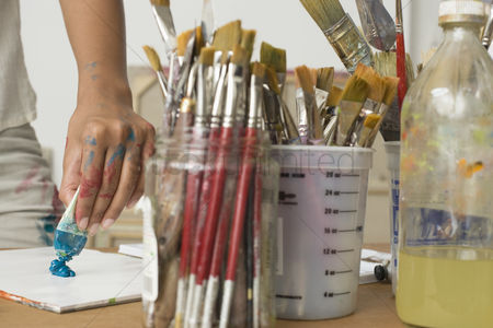Arts : Artist squeezing paint onto palette
