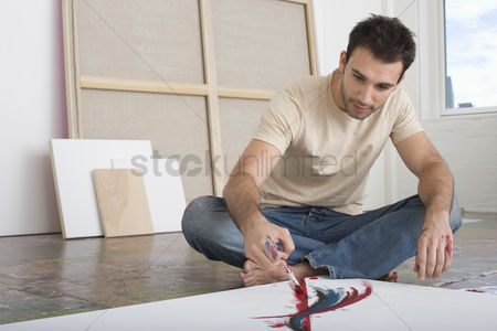 Paint brush : Artist working on canvas on floor of studio