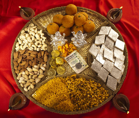 God : Assorted diwali sweets and snacks with diwali diyas