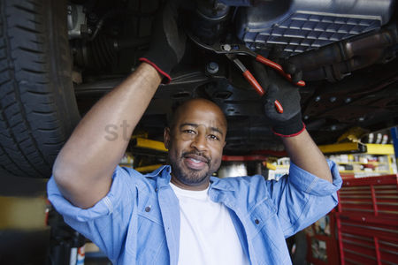 Posed : Auto mechanic beneath a car