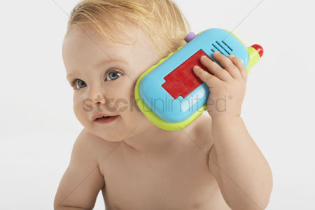 Head shot : Baby listening to toy telephone