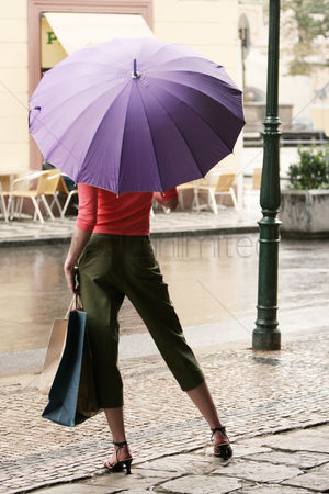 Shopping : Back shot of a lady in high heels holding a purple umbrella and carrying paper bags