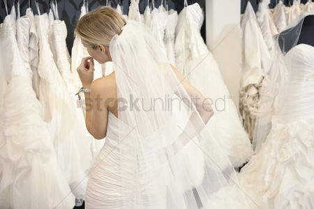 Shopping : Back view of a young woman in wedding dress looking at bridal gowns on display in boutique