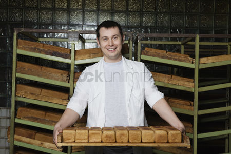 Posed : Baker carrying loaves of fresh bread