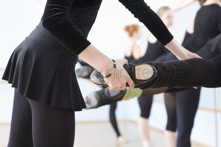 Dance : Ballet teacher adjusts foot positions at the barre