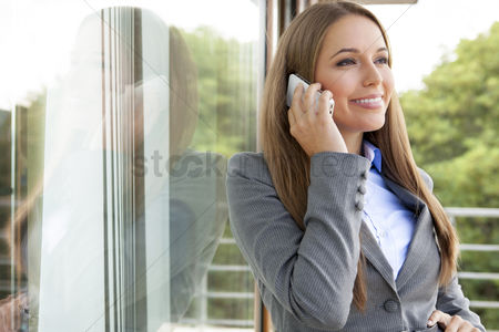 Cell phone : Beautiful businesswoman using cell phone by glass door