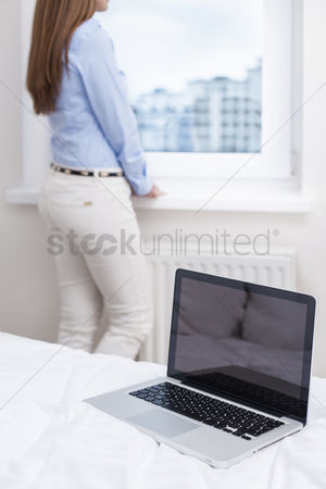 Employee : Beautiful woman staring out of window with laptop in foreground