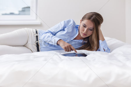Furniture : Beautiful woman using tablet computer on her bed