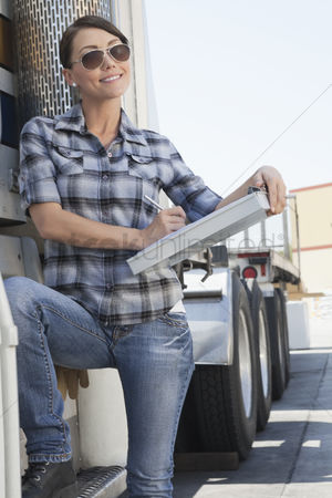 Land : Beautiful woman writing on clipboard while standing by a flatbed truck