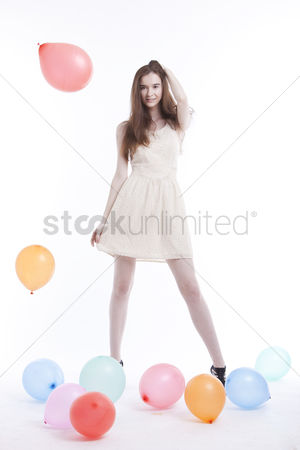 Celebration : Beautiful young woman in dress with balloons on floor against white background