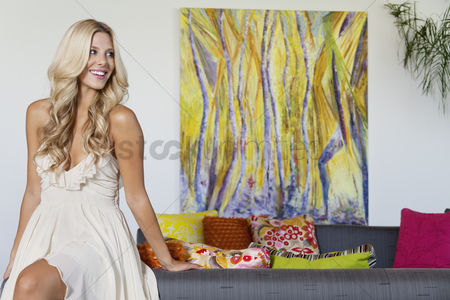 Arts : Beautiful young woman looking away with painting in background