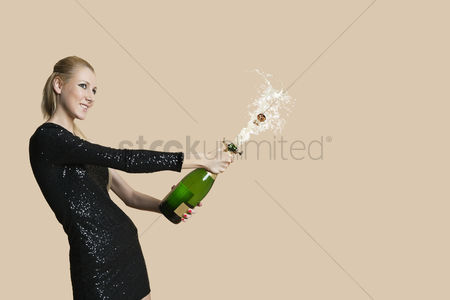 Women : Beautiful young woman uncorking champagne bottle over colored background