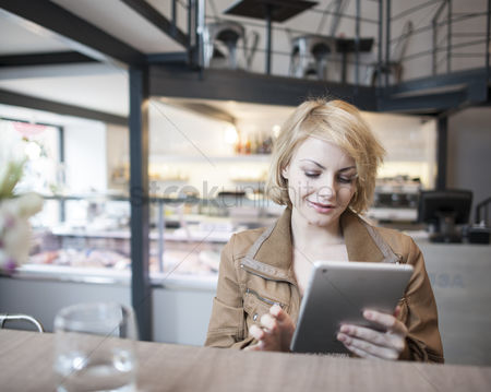 Internet : Beautiful young woman using digital tablet in cafe