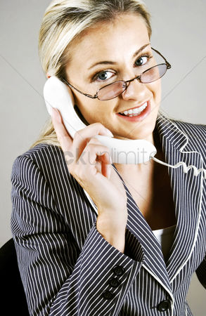Answering calls : Bespectacled business woman talking on the phone