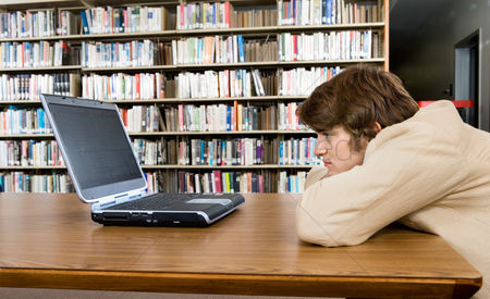Study : Bored male student with laptop at library
