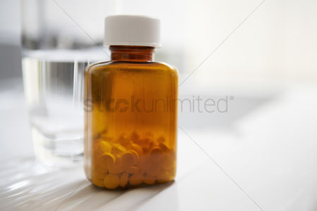 Medication : Bottle of pills next to water on table close up