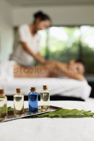 Relaxing : Bottles of massage oil  woman receiving back massage in the background