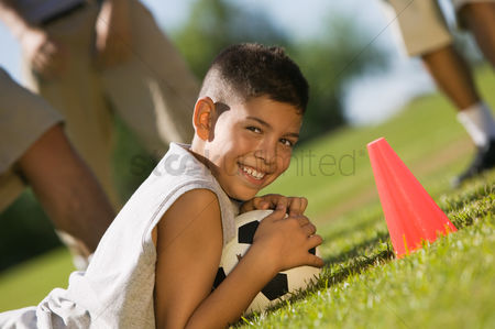 Grass background : Boy  13-15  lying down on grass holding soccer ball