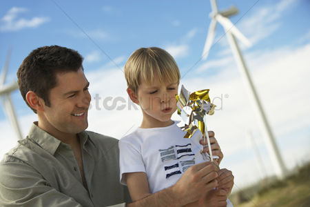 Blowing : Boy  7-9  blowing toy windmill with father at wind farm
