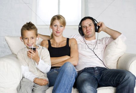 Children : Boy and father listening to music with his mother sitting in between