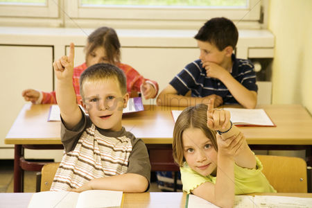 School : Boy and girl raising their hands to answer question