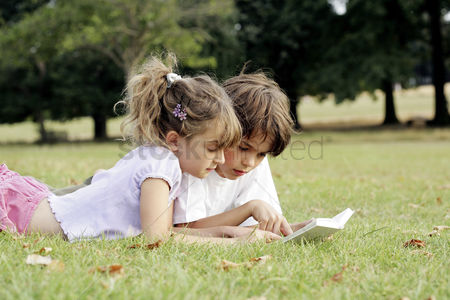 Grass : Boy and girl reading a book