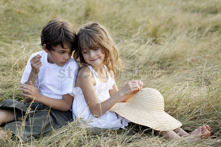 Grass : Boy and girl sitting back-to-back