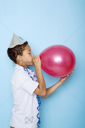 Blowing : Boy blowing up a balloon