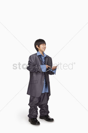 Having fun : Boy dressed up as businessman using tablet