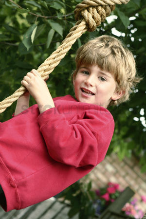Having fun : Boy holding on to a rope