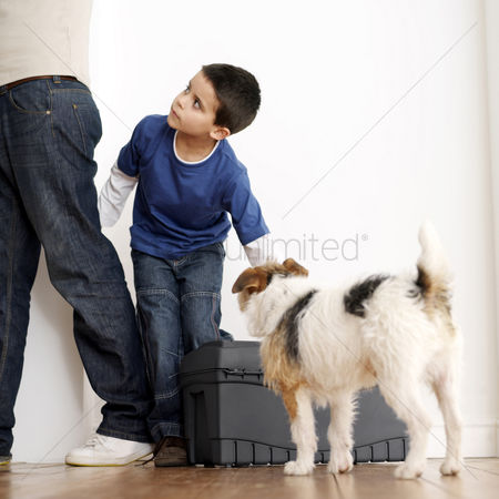 Strong : Boy looking at his father while trying to carry toolbox