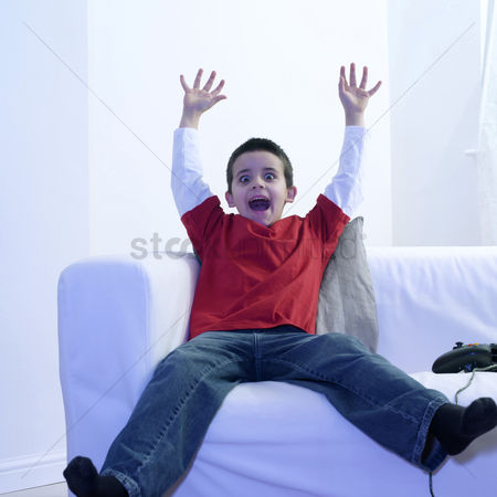 Children playing : Boy raising his hands while playing with video game console