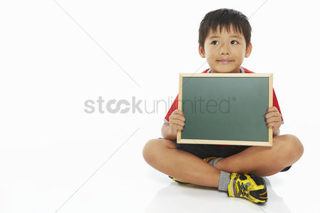 Blank : Boy sitting and holding up a blackboard