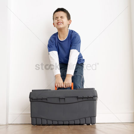 Strong : Boy trying to carry up a toolbox