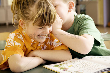 Young boy : Boy whispering something into girl s ear