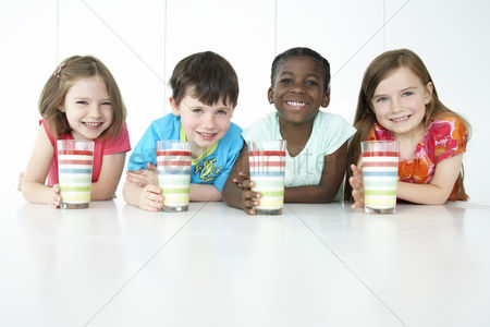 Group portrait : Boys and three girls  5-6  sitting at table holding colourful glasses smiling portrait
