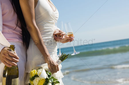Celebrating : Bride and groom with champagne at ocean  close-up