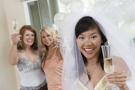 Toasting : Bride holding champagne toasting with friends at bridal shower
