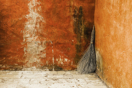 Weathered : Broom leaning against the wall in a rural courtyard