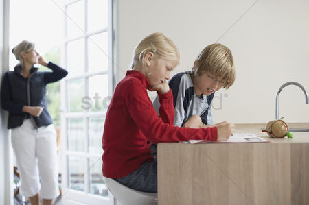 Interior background : Brother and sister doing homework in kitchen