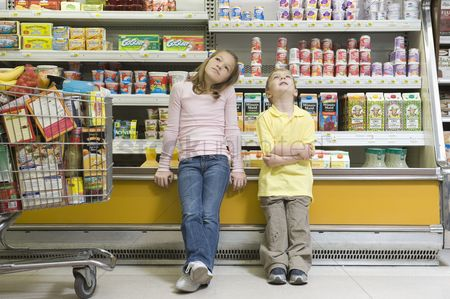 Supermarket : Brother and sister sit side by side on fridge counter in supermarket