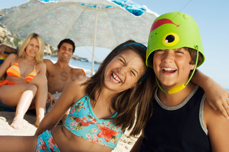 Pre teen : Brother and sister sitting on beach arm around boy with bucket on head