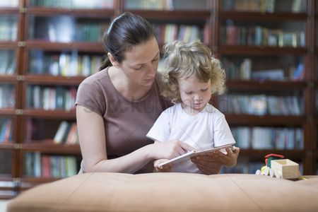 Curly hair : Brunette woman teaches blonde toddler how to read