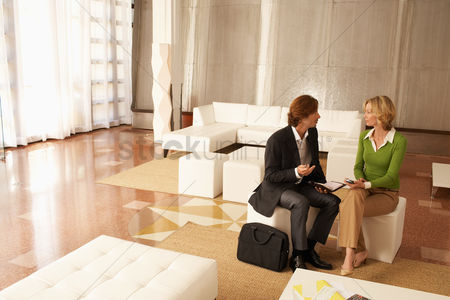 Smiling : Business couple talking in living room