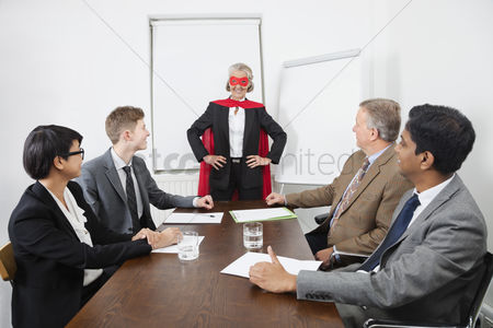 Office worker : Business leader as superhero in front of colleagues at meeting in conference room