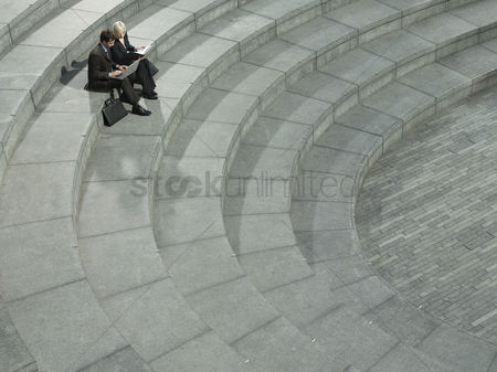 Stairs : Business man and woman sitting on spiral stairs using laptop elevated view