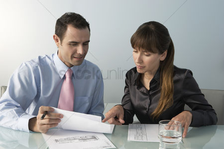 Mid adult man : Business man and woman working at table in office
