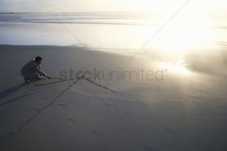 One man only : Business man drawing arrow in sand on beach elevated view