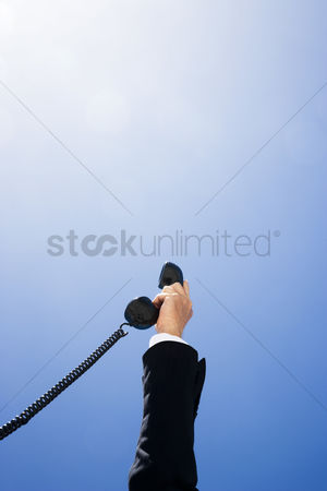 Land : Business man holding telephone receiver against sky close up of hand